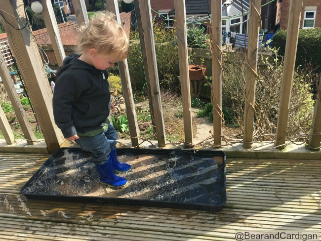Toddler stood in plant tray full of water