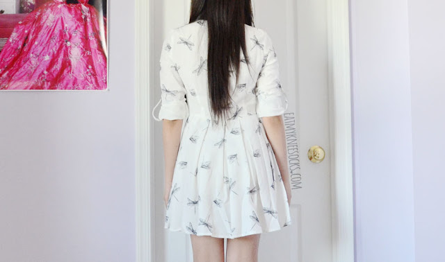 Details on the white long sleeve fold-collar buttoned dragonfly print shirtdress from SheIn, featuring contrast piping, convertible sleeves, a detached neck tie, and a pleated skirt.