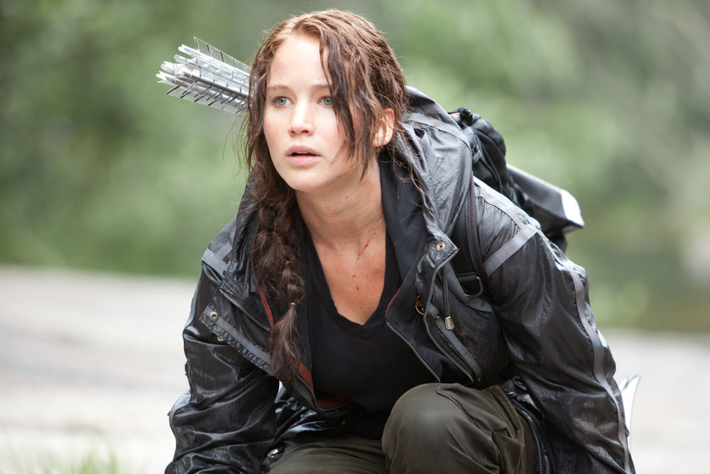 Jennifer Lawrence as Katniss Everdeen crouching down in forest with arrows on her back