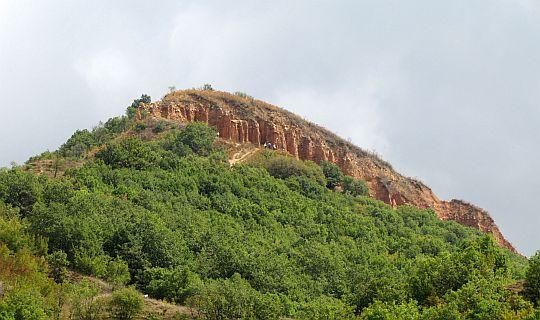 Zbliżenie na szczyt drugiego wzniesienia. W jego zboczach widoczne są wytwory natury.