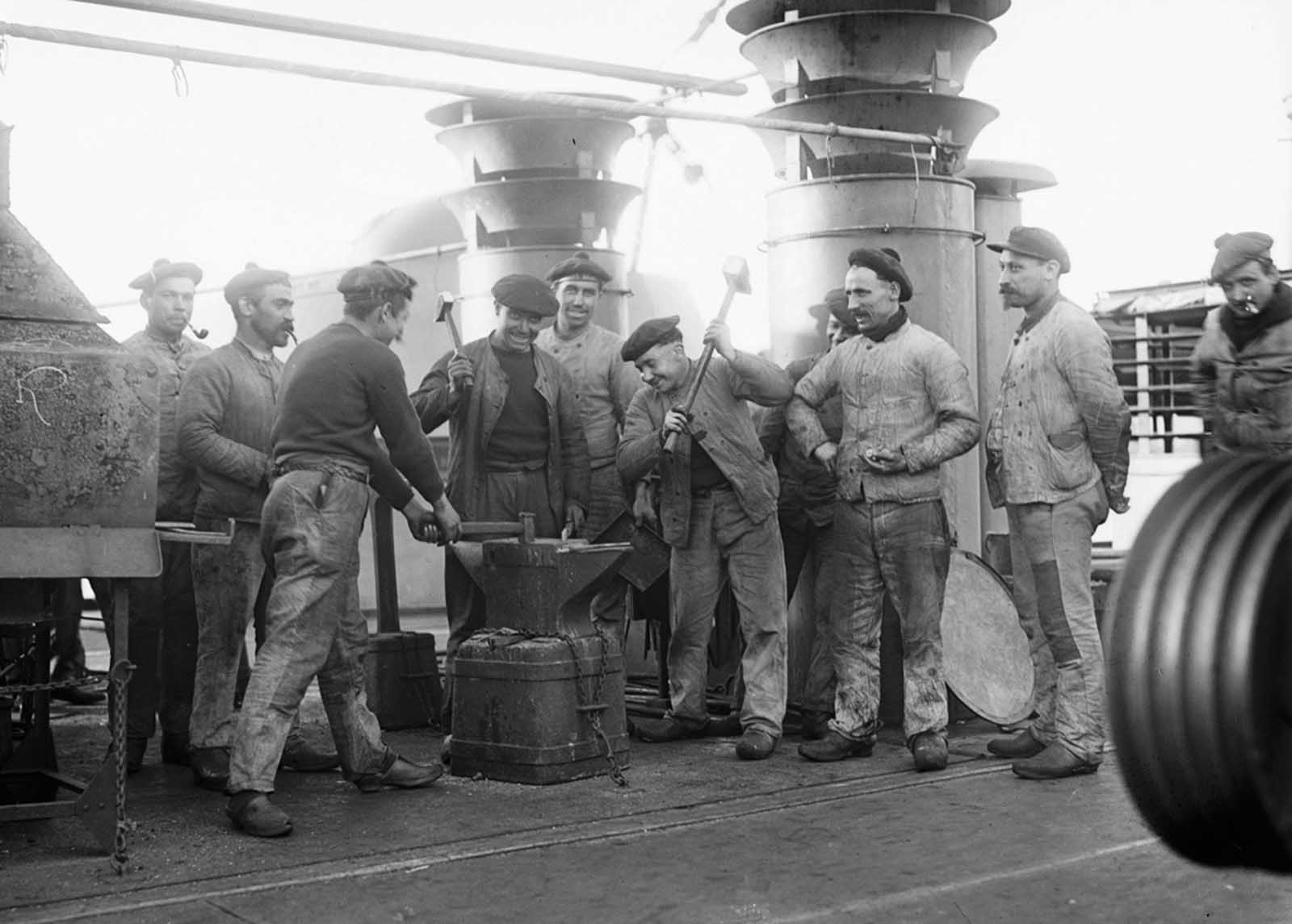 Sailors aboard the French cruiser Amiral Aube pose for a photograph at an anvil attached to the deck.