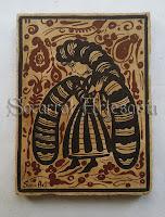 Este ejemplar es de los más bellos en cuanto a diseño y sencillez al mismo tiempo se refiere. Nos muestra una dama con larga melena y mangas anchas que apenas dejan ver los brazos. Pintado enteramente con óxidos de hierro y manganeso. Soc-Art