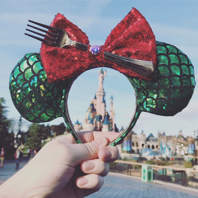 A pair of Little Mermaid themed Ariel ears held up in from of the castle