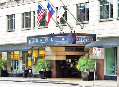 Flag-adorned entrance of Magnolia Hotel at 1100 Texas Ave, Houston, TX 77002