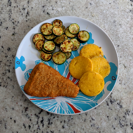 image of a plate sitting on my kitchen counter holding a piece of breaded fish, some sauteed zucchini, and polenta