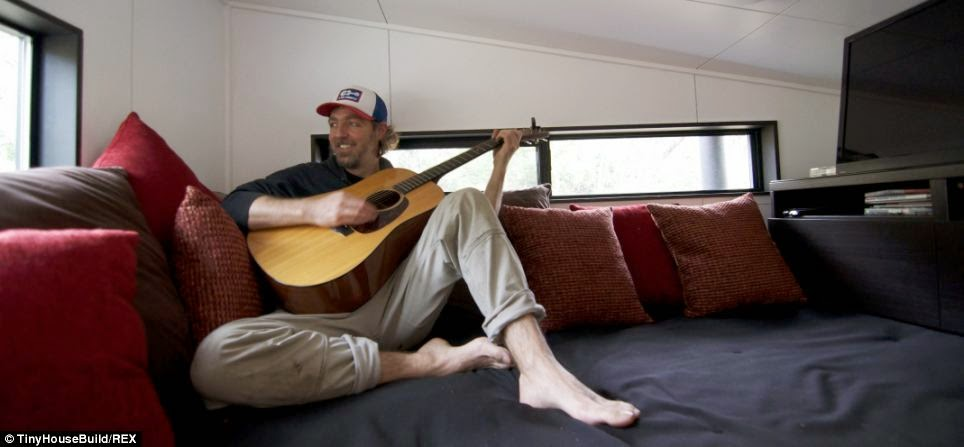 Mr. Morrison plays his guitar and relaxes in his new lounge, which his wife says has brought them closer as a family - This Couple Got Out Of The Rat Race. And Built This Tiny Home For $33K.
