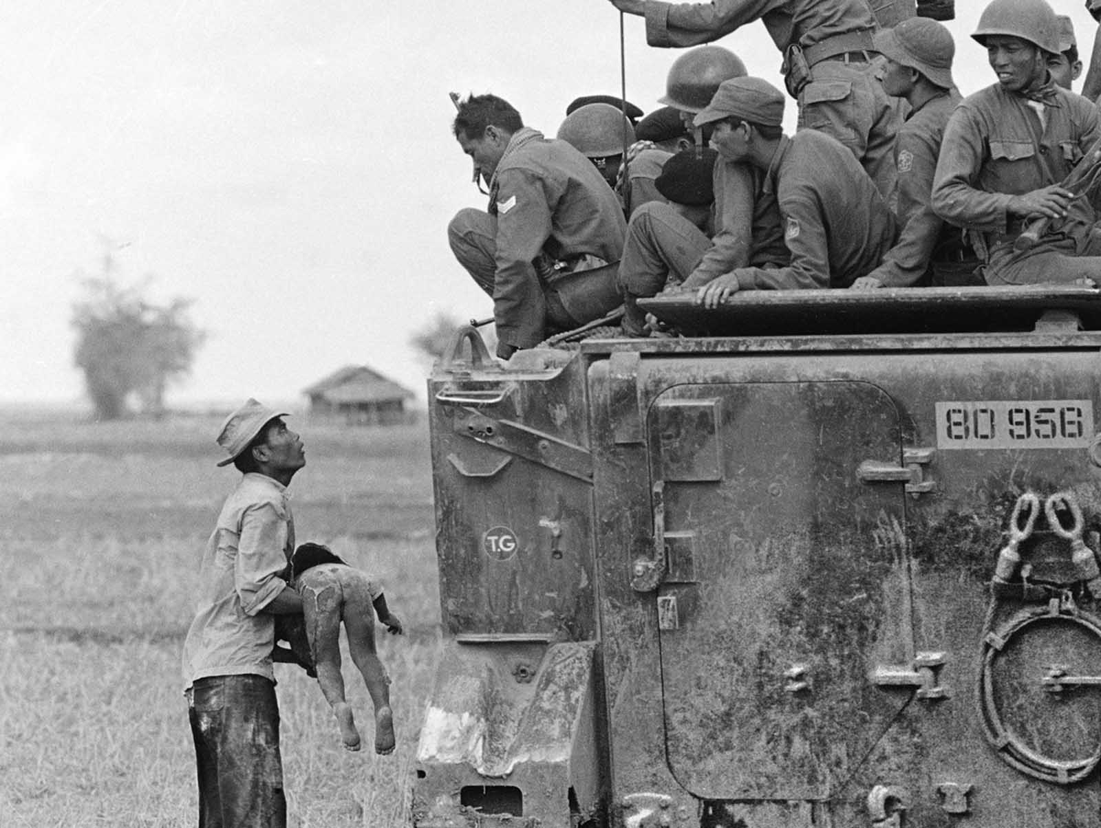 A father holds the body of his child as South Vietnamese Army Rangers look down from their armored vehicle on March 19, 1964. The child was killed as government forces pursued guerrillas into a village near the Cambodian border.