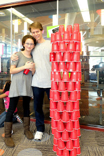 Melandie and dad George stand proudly beside a cyndrical tower made of red plastic cups.