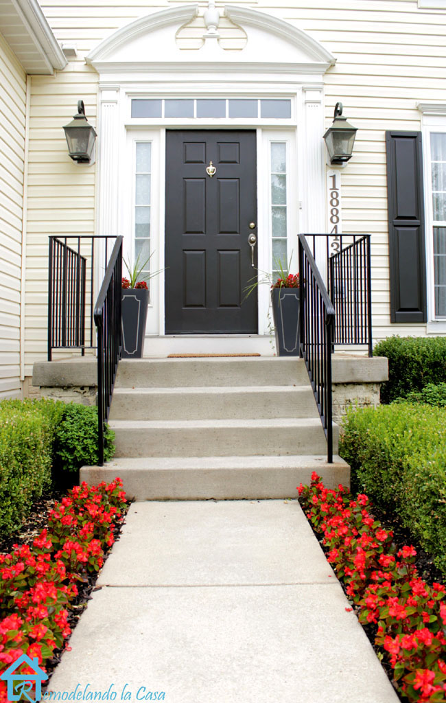 Front porch with metal railing, green door, and red annual flowers