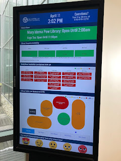 Interactive screen display showing computer availability, meeting room availability, crowd-size in study spaces, and customer satisfaction emojis