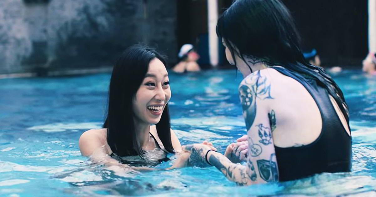 Dos risueñas mujeres chinas con tatuajes se bañan en una piscina