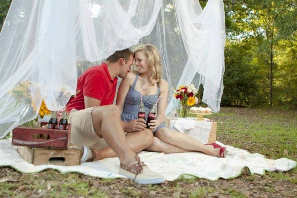 An adorable couple having a picnic in the park with vintage soda bottles and a gorgeous lacy canopy