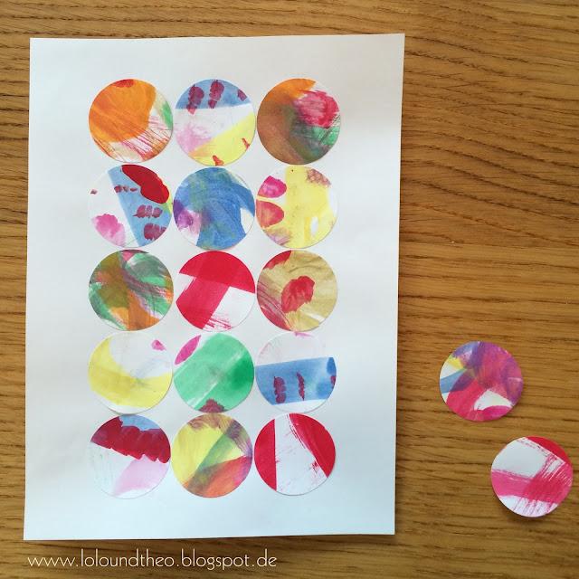 ausgeschnittene Kreise aus bemaltem Papier auf weißes Blatt geklebt