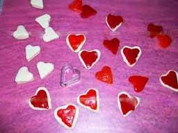 Красные сердечки нарезаем из паприки или сладкого перца и выкладываем их поверх маленьких сердечек из теста.