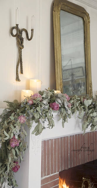 Dried garland on mantel in living room with candles