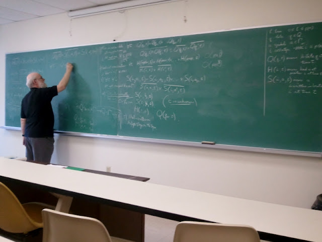 Photo of a man writing mathmatical symbols on a chalkboard.
