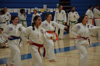 Four martial arts women doing a Taekwondo poomse