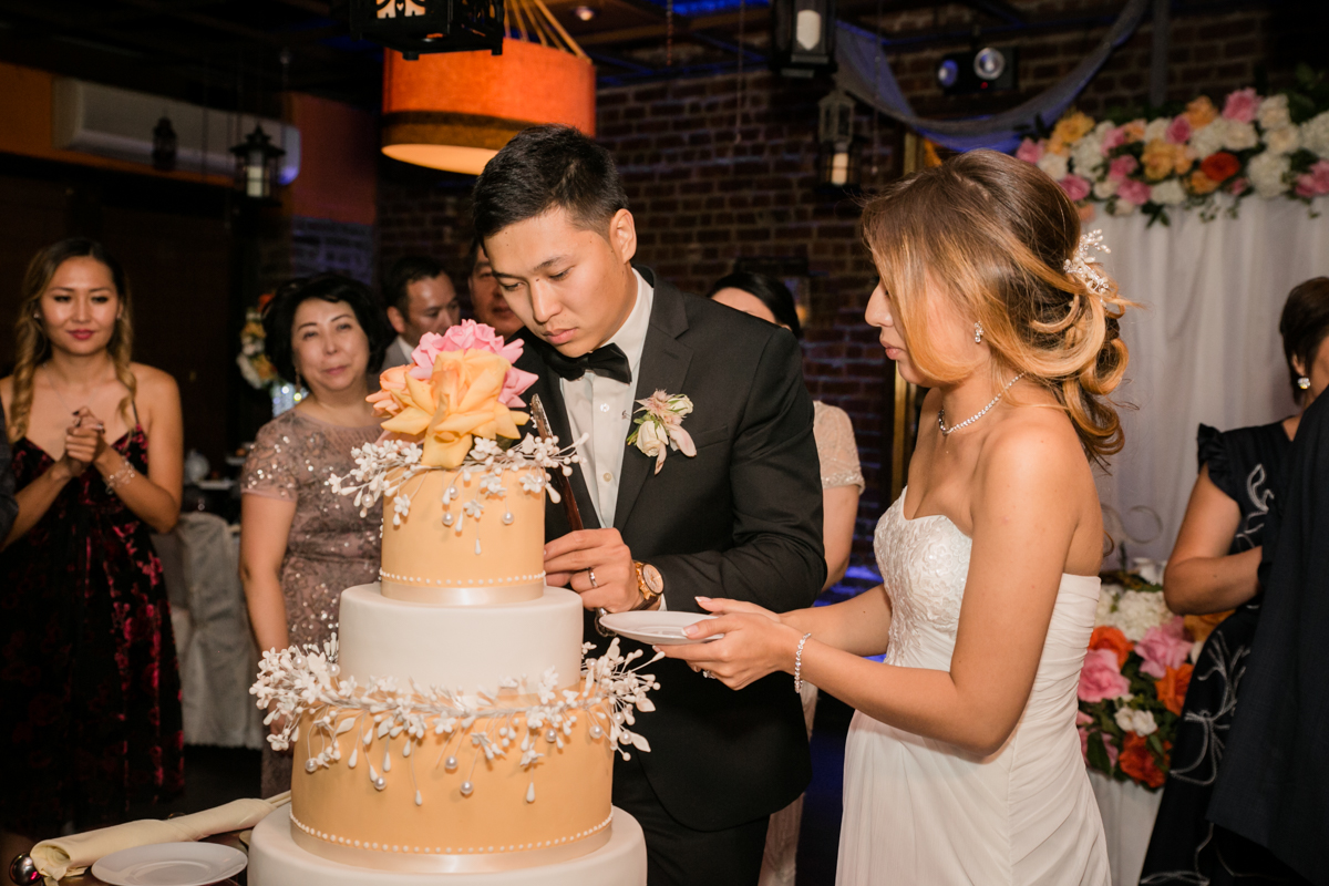 The couple pay special attention while cutting the cake to feed each other.