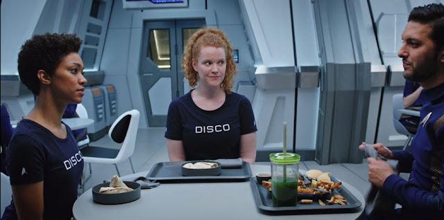 Tilly y Burnham llevan camisetas azules donde se lee DISCO, tienen platos redondos con 2 burritos cada una, y Sarek tiene un batido verde, hamburguesa y vemos patatas