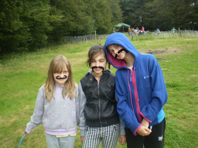 three children in fake moustaches