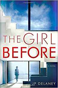 Book cover for the novel THE GIRL BEFORE, by JP Delaney. The cover shows the floor-to-ceiling window and open front door of a modern custom home. A woman is standing in shadow in the doorway.