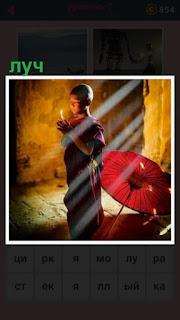 в помещении стоит мальчик и молится под лучами солнца из окна