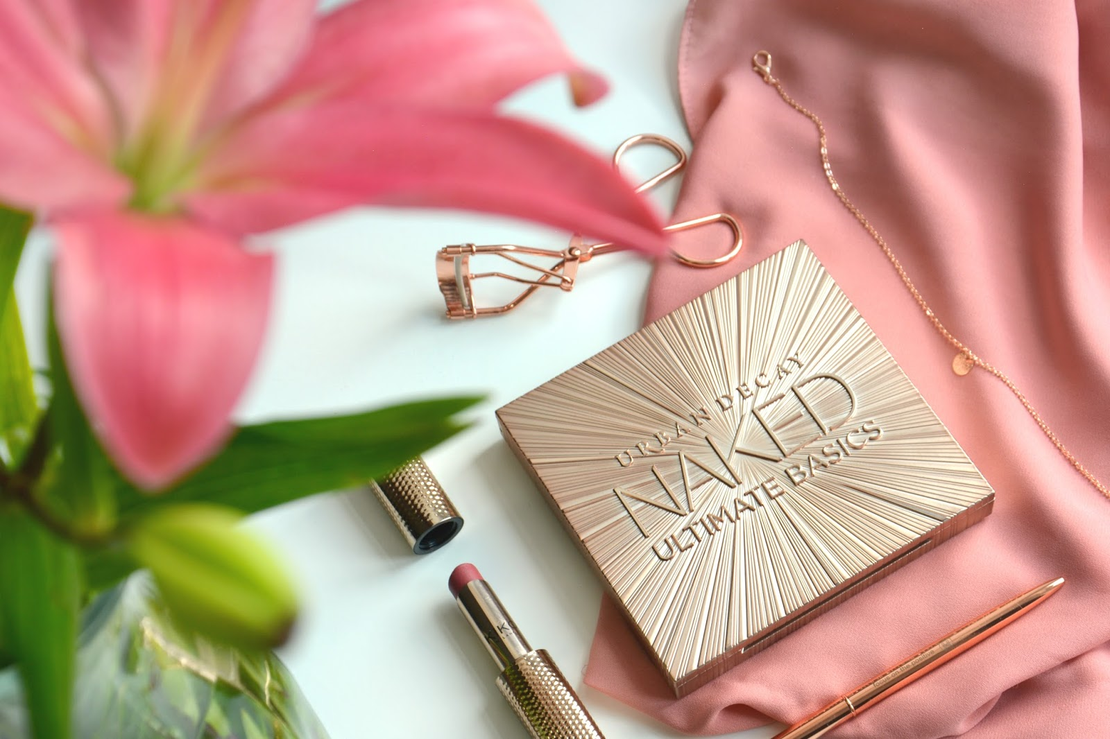 Urban Decay Naked Ultimate Basics Eyeshadow Palette; Kiko Lipstick; Happy Planners Pen;  Primark Necklace; Primark Rosegold Eyelash Curler; Fresh lilies