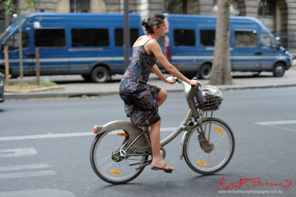 Woman in summer dress and sandals rides a Vélib city bike. Paris photos by Kent Johnson for Street Fashion Sydney.