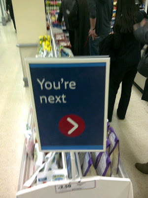 Tesco Youre Next sign, you're next, chilling sign, store supermarket line queue, directional signage