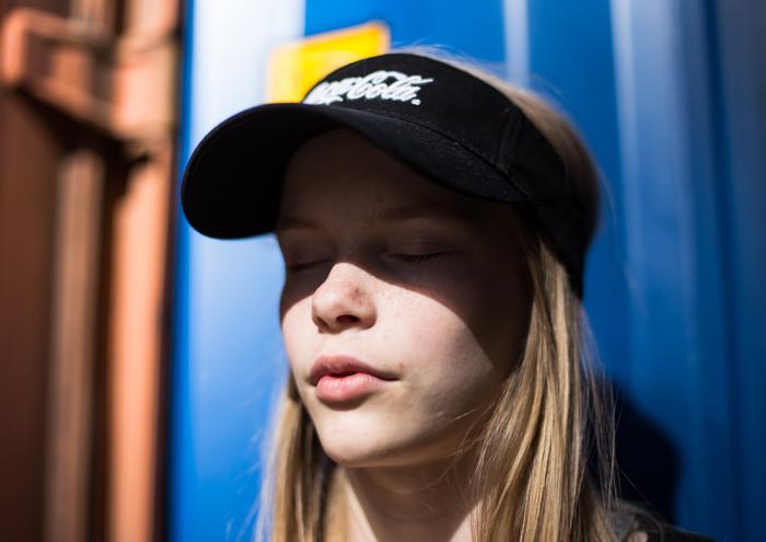 pitkähiuksinen tyttö ottaa aurinkoa lippis päässä henkilökuva potretti valokuvaus_