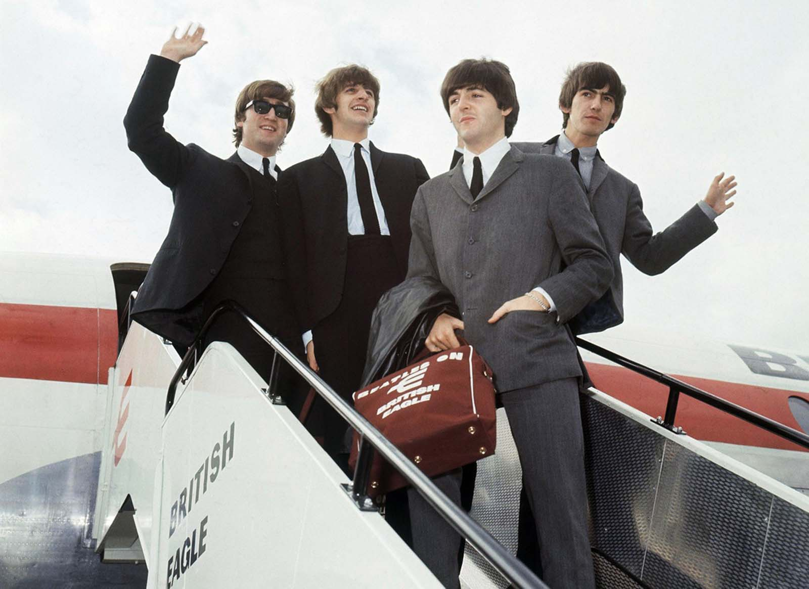 The Beatles leave London airport in 1964. From left: John Lennon, Ringo Starr, Paul McCartney and George Harrison. Enthusiastic fans welcomed the Beatles in airports and concert halls around the world in 1964, as Beatlemania swept the globe.