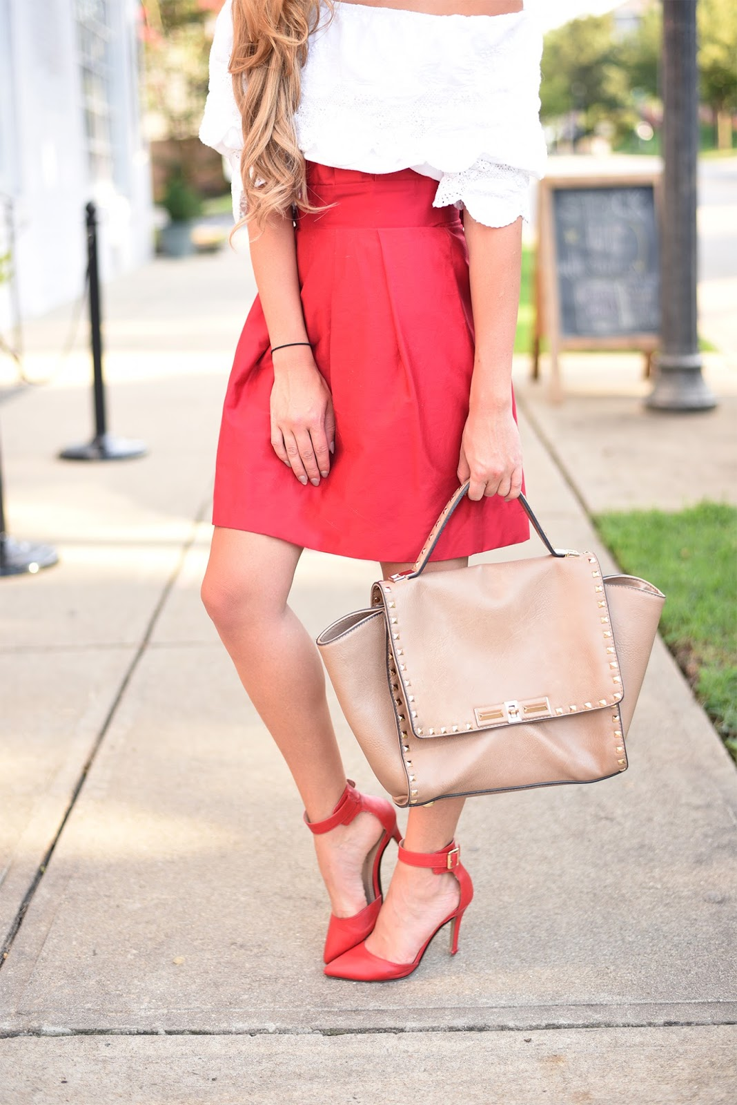 Red-pleated-skirt-pointed-toe-ankle-strap-heels-and-studded-tote-purse