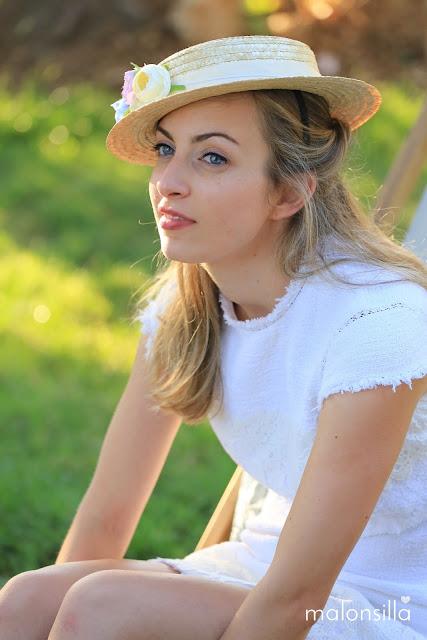 Invitada boda, primer plano, sentada en el campo con vestido corto y sombrero de paja tipo canotier