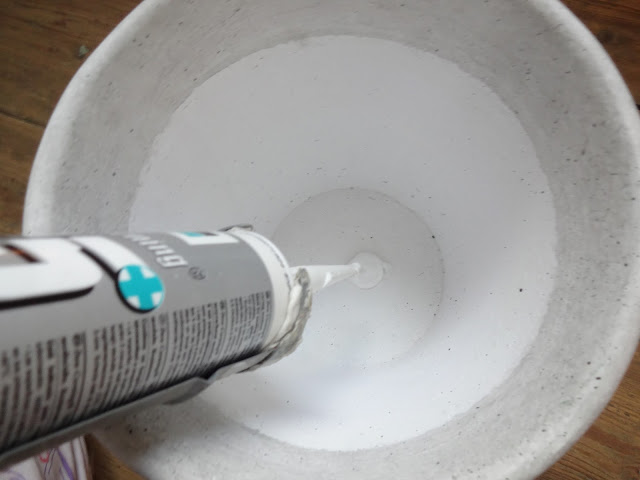 Using sealant to fill a hole in a plant pot