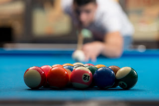 A closeup of a rack of pool balls and a man getting ready to break them