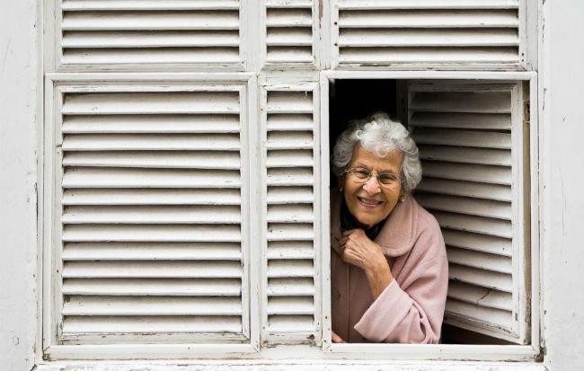 Donna anziana che sorride alla finestra