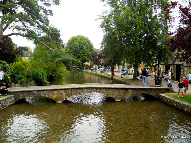 Bourton on the Water, A lovely little town in Cotswolds. Bourton on the Water is the a tidy Cotswolds town that sits on both the banks of the river Windrush. It is a major tourist stop and is often referred to as the Venice of the Cotswolds because of the river running through it and its low, stone bridges. This was the prettiest of all the Cotswolds towns that we visited on this trip.Our tour bus dropped us at the parking lot and we had to walk to the centre of the town where the river flows. On the way we came across several trademark Cotswolds cottages and this close called Foxes Close. Close in British Sense means a narrow alley or pathaway.People relaxing on the banks of the river Windrush. Your would've seen similar scenes on handouts distributed by various builders of apartment complexes. They lead the buyers to believe that the lifestyle in the apartment complexes will be as laid back and chilled out as in some of these British Towns.A low stone bridge on the river Windrush. You find numerous cafes and Souvenir shops on both the banks of the rivers. Children playing freely in the shallow river and fishermen idling around with their fishing rods doing their work for them are part of the common weekend scene in the town. An alley with yellow cottages on both the sides. Tidy grey streets and yellow walls are in stark contrast with each other. People picnicking on the banks of the river. You'll see people of all age-groups having fun. The best part of this lifestyle is that no one judges the others too much. Old people are entitled to having as much fun as the youngsters. My Friend Hannah. She was constantly attracted to shops selling antiques and vintage stuff. Me and Kelsey were equally interested/disinterested in everything so we had no issues in following her around. Cotswolds was the best part of this trip and Bourton on the Water was the best town we visited in the Cotswolds.Cotswolds, Bourton on the Water, River Windrush, UK, Travelling Camera, Travel
