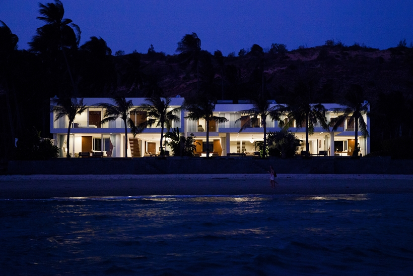 Modern beach house at night from the sea