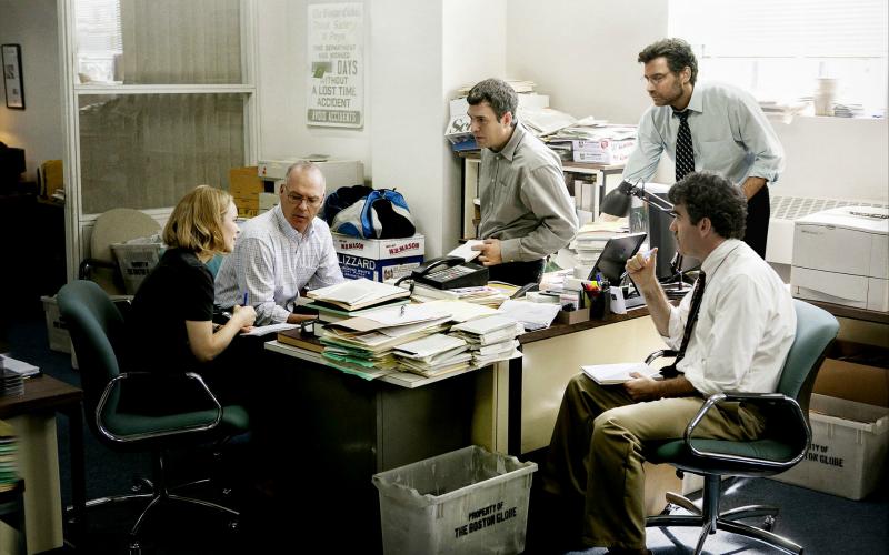 Na imagem: em torno de uma mesa cheia de papéis e materiais de escritório, cinco jornalistas (uma mulher, quatro homens) discutem algo importante.