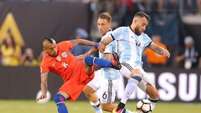 Pemain Chile, Arturo Vidal, berjibaku memperebutkan bola dengan pemain Argentina