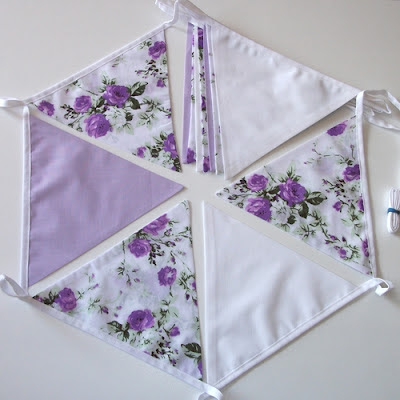purple roses with lilac and white bunting