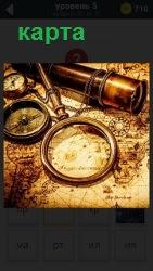 На столе развернута карта. Сверху положены труба, лупа и компас, происходит выбор маршрута