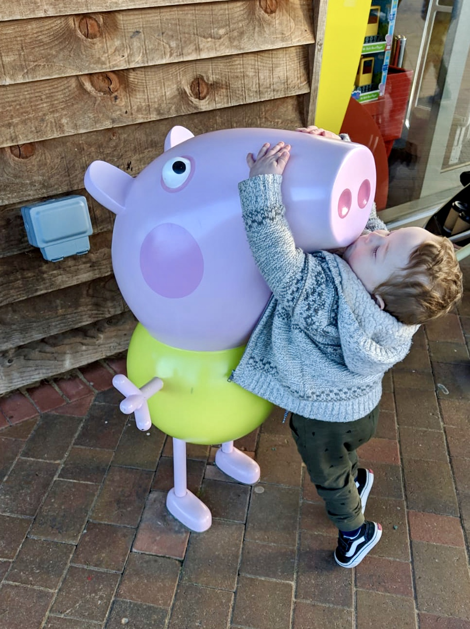 toddler boy standing on tiptoes and kissing peppa pig statue at peppa pig world paultons park