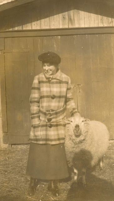 A young woman (unidentified) models a terrific plaid jacket. A sheep adds to the wooly ambiance of the photo.