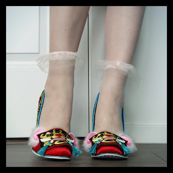 wearing Irregular Choice red Ruby Envelope court shoes front