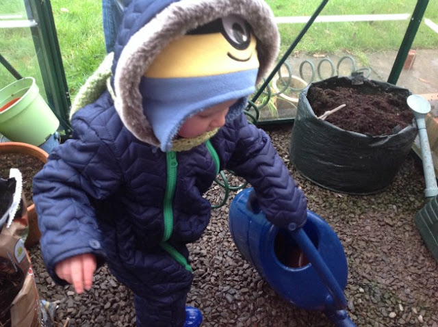 toddler with watering can in green house all wrapped up with scarf and hood