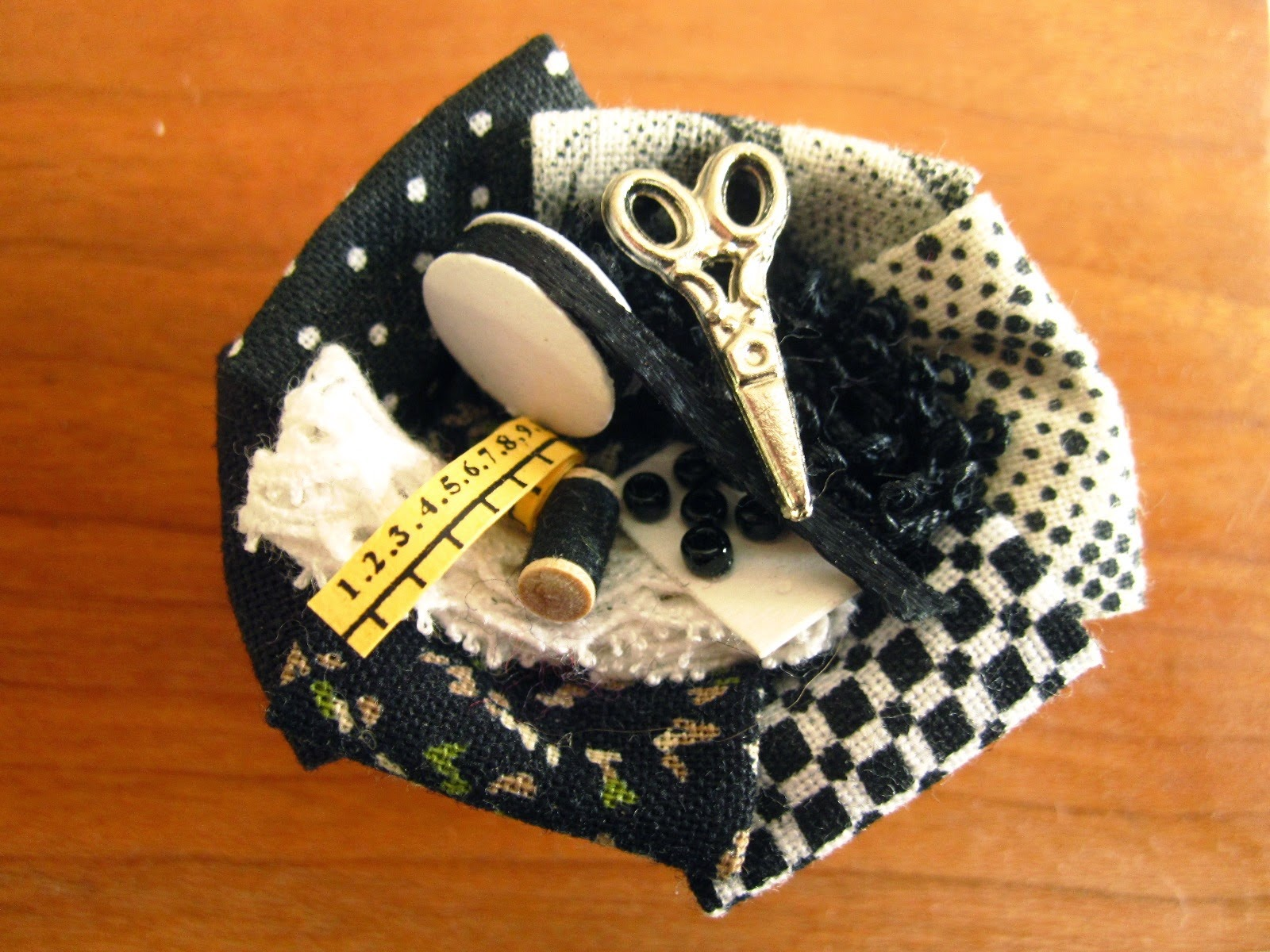 Dolls' house miniature sewing basket with various fabrics and notions in black and white, plus scissors and a tape measure.