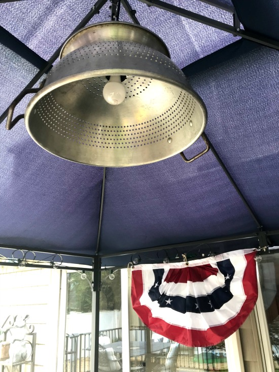 Farmhouse colander light hanging outdoors in the gazebo