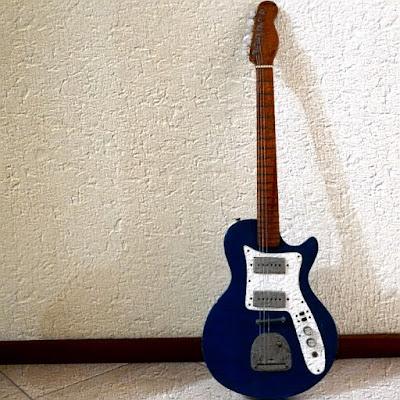 Guitarra diante de uma parede.