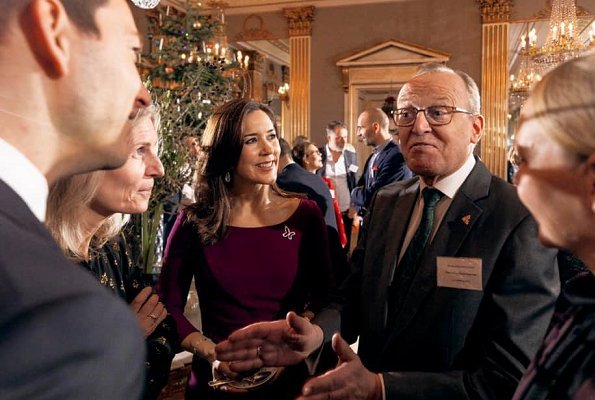 Crown Princess Mary wore Prada purple knee-length dress. The Princess hosted a Christmas reception for Mary Fonden. She wore her Prada purple dress